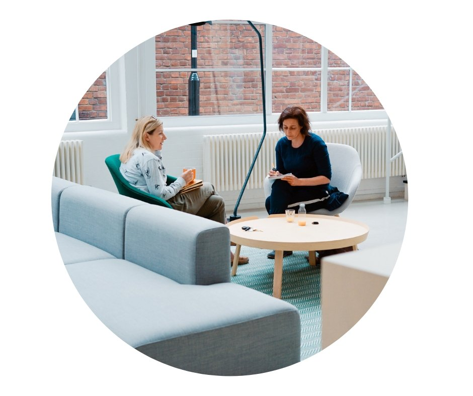Two people sitting in a comfy area talking