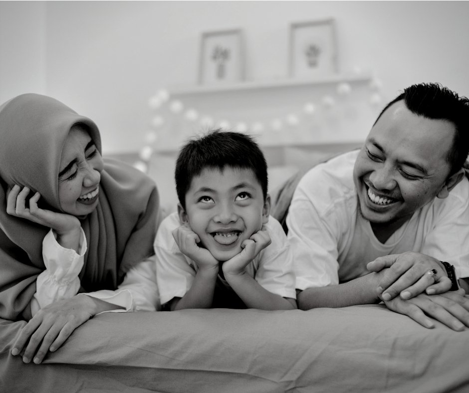Black and white photo of an ethic family smiling at one another