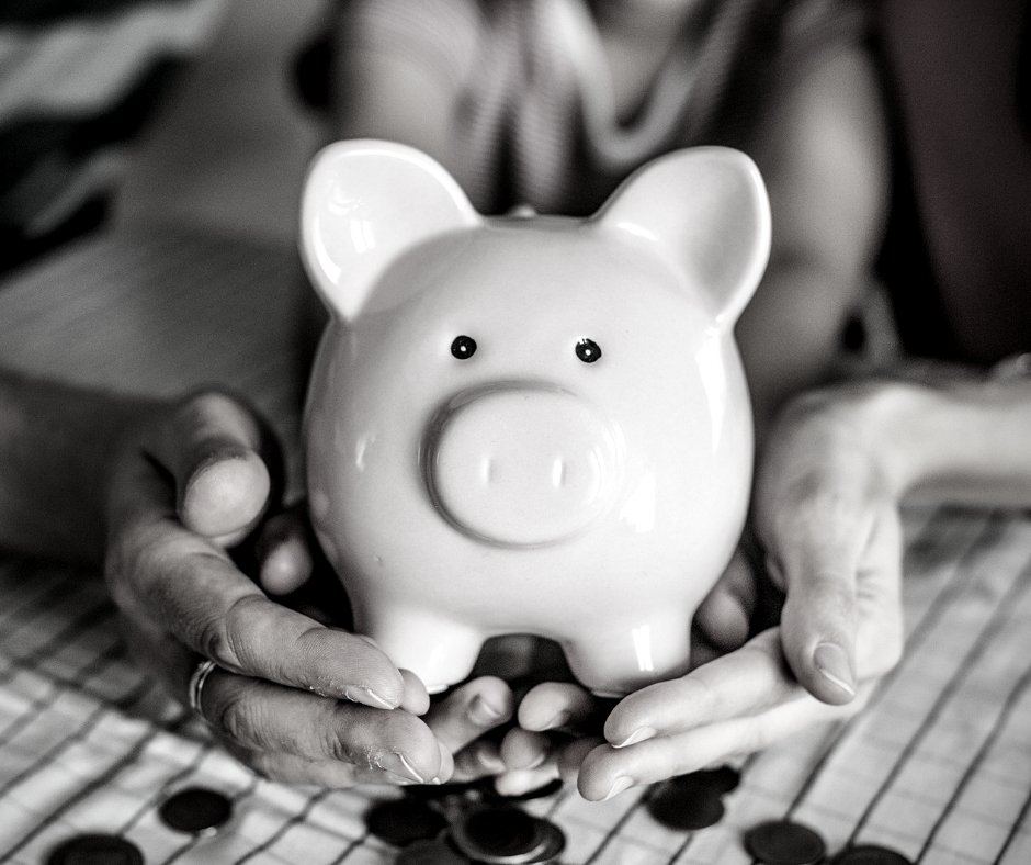 Black and white photo of a piggy bank held by a family