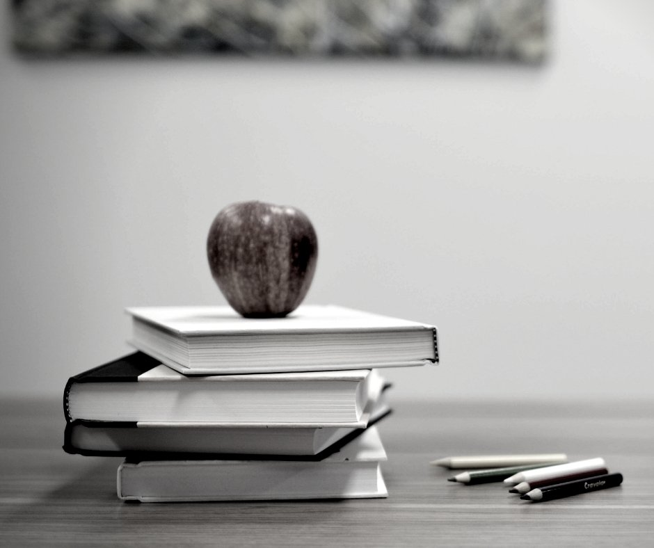 Black and white photo of school books and pencils and an apple on a desk