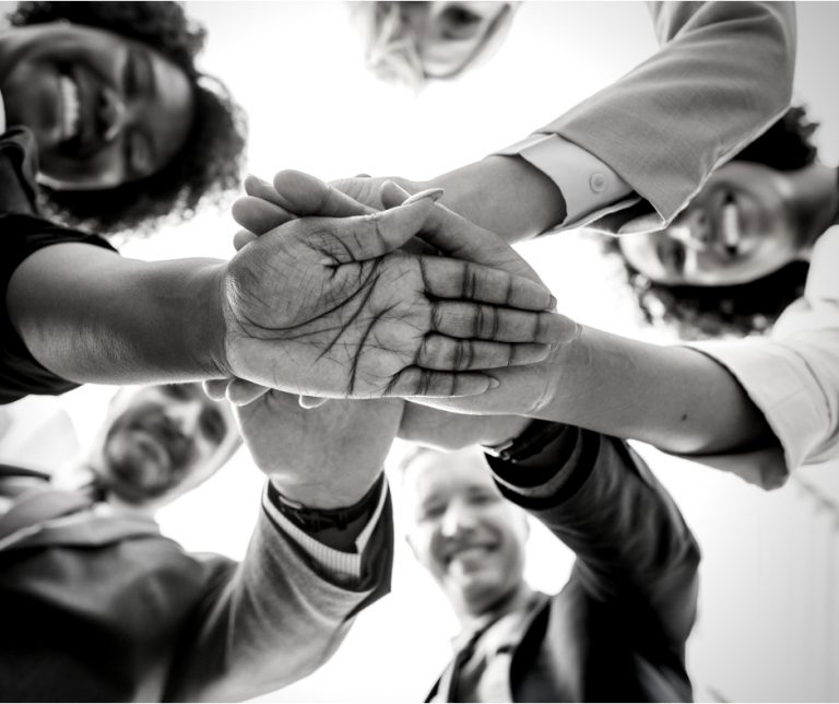 Black and white photo of a mix of professionals joining hands