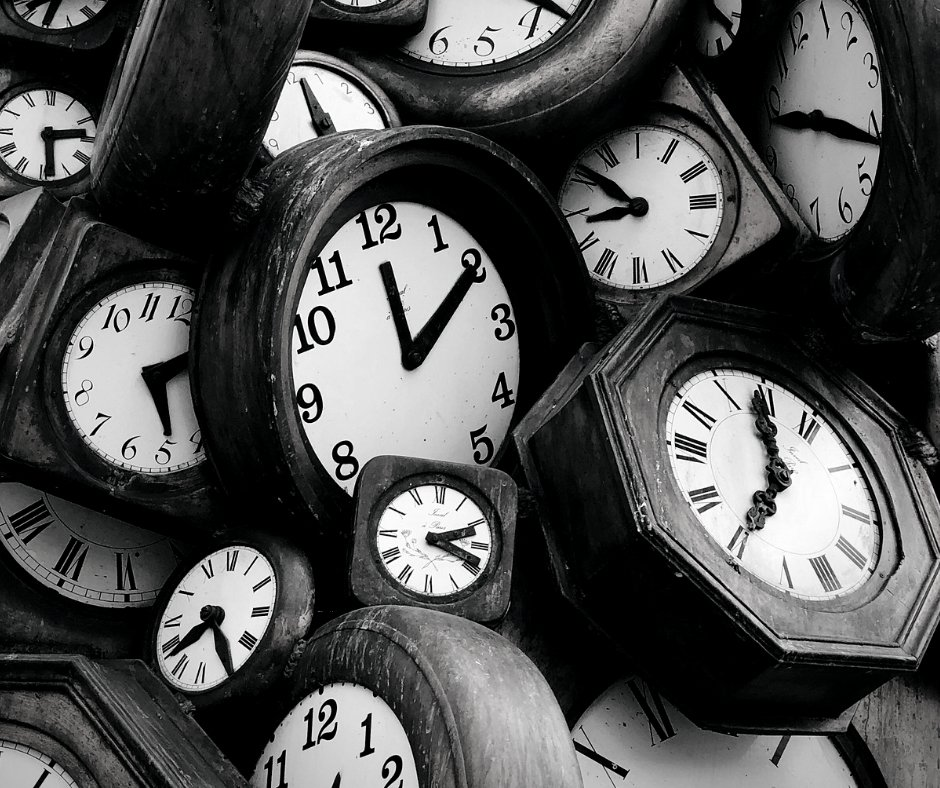 Black and white photo of a collection of clock faces pilled on top of one another