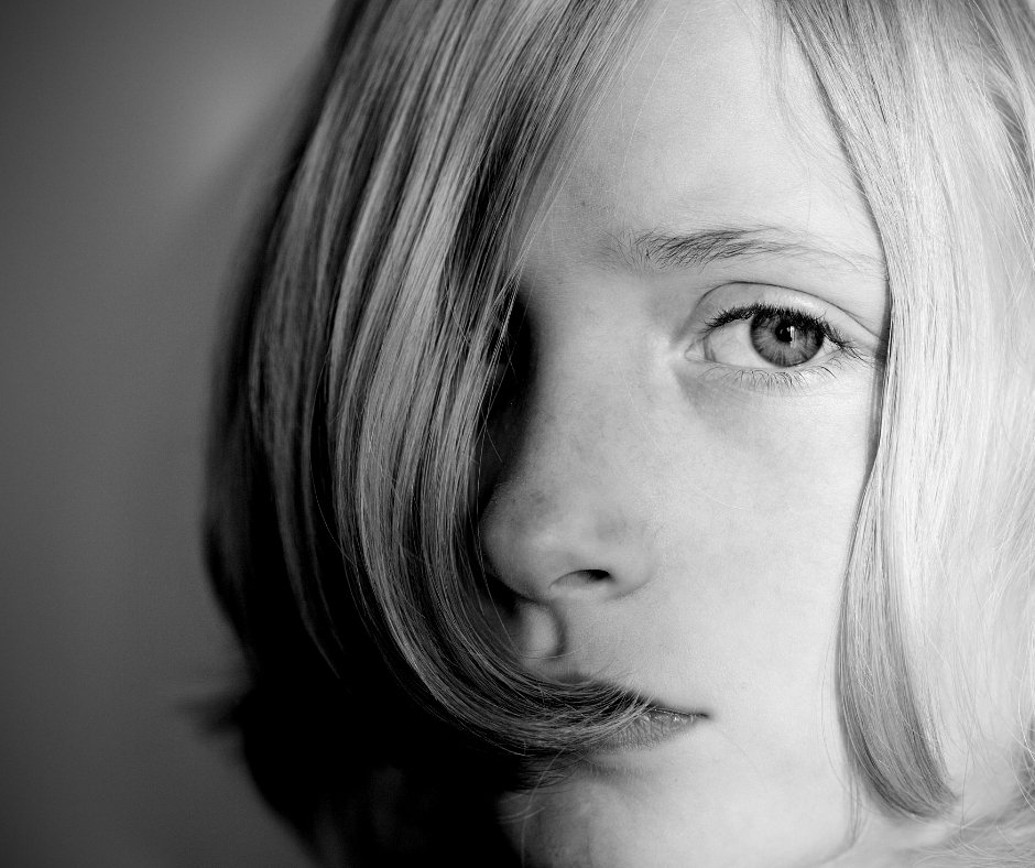Black and white photo of a blond hair child looking sad